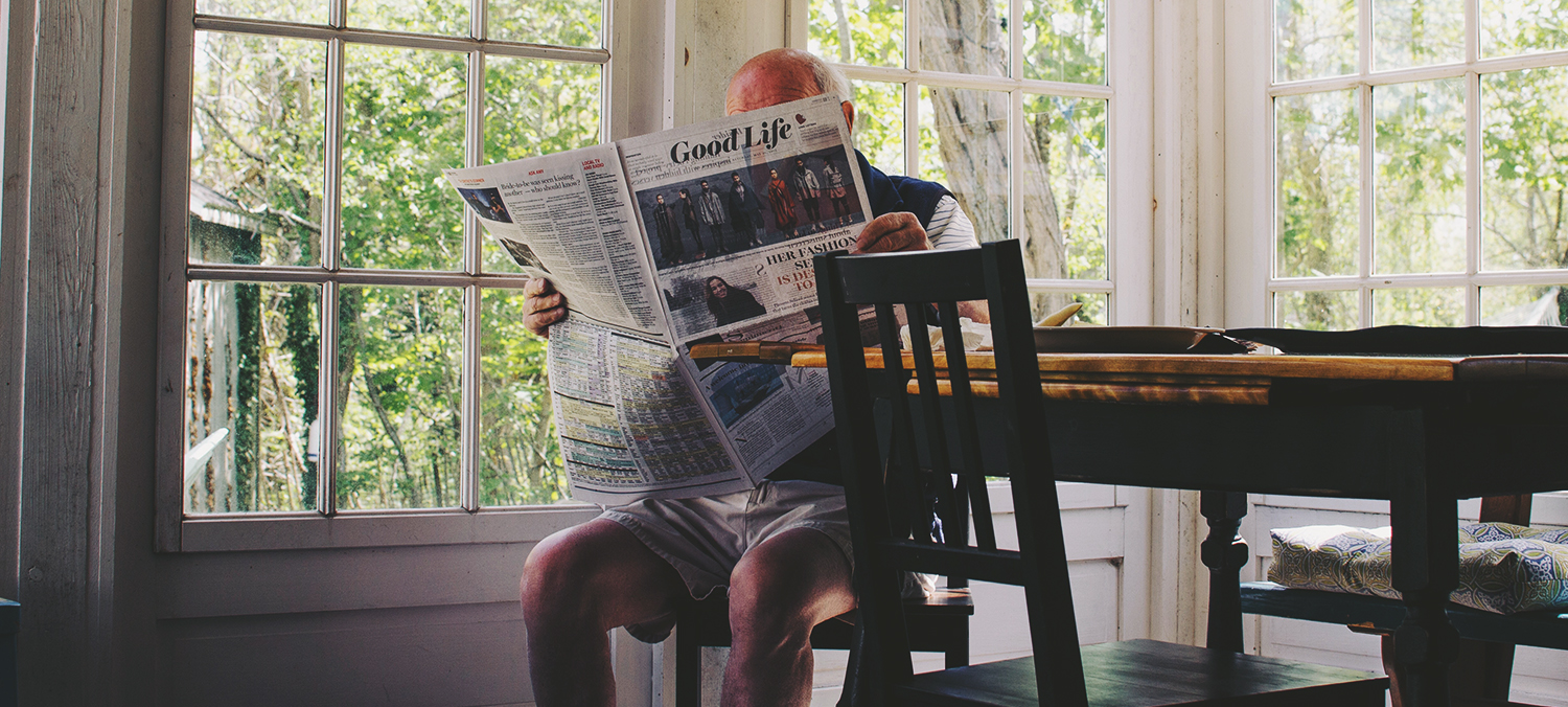 "elderly man reading a newspaper titled ""The Good Life"""
